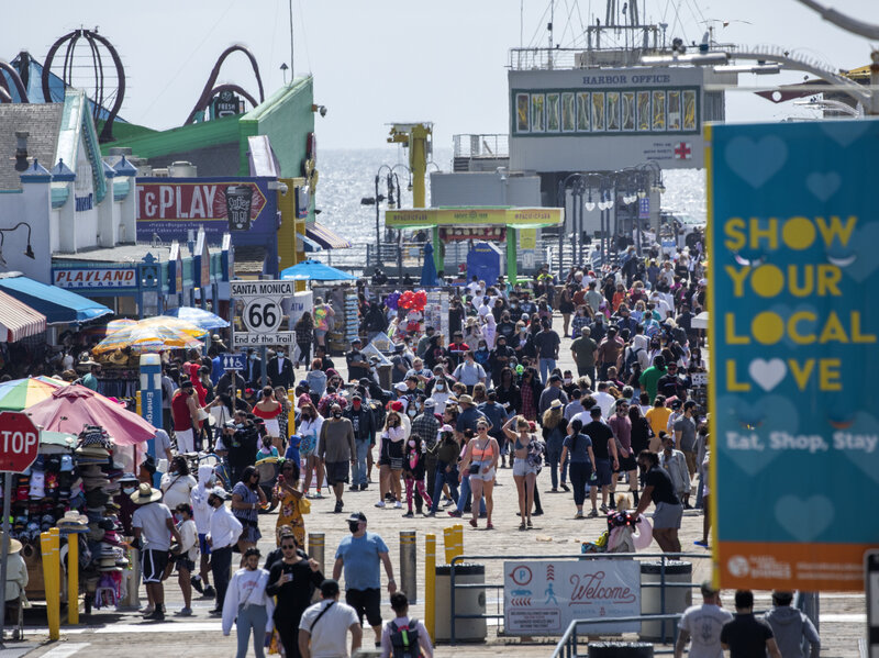 SANTA MONICA, CA - APRIL 05: Visitors stroll along the Santa Monica Pier on Monday, April 5, 2021 as Los Angeles County entered the less strict orange tier allowing more places to open and inviting more people to venture outdoors. Photographed in Santa Monica Pier  in Santa Monica, CA. (Myung J. Chun / Los Angeles Times via Getty Images)