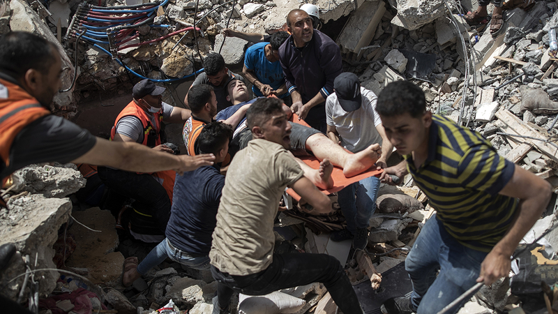 Palestinian rescue a survivor from under the rubble of a destroyed residential building following deadly Israeli airstrikes in Gaza City, Sunday, May 16, 2021. The Israeli airstrikes flattened three buildings and killed at least 26 people Sunday, medics said, making it the deadliest single attack since heavy fighting broke out between Israel and the territory's militant Hamas rulers nearly a week ago. (AP Photo/Khalil Hamra)